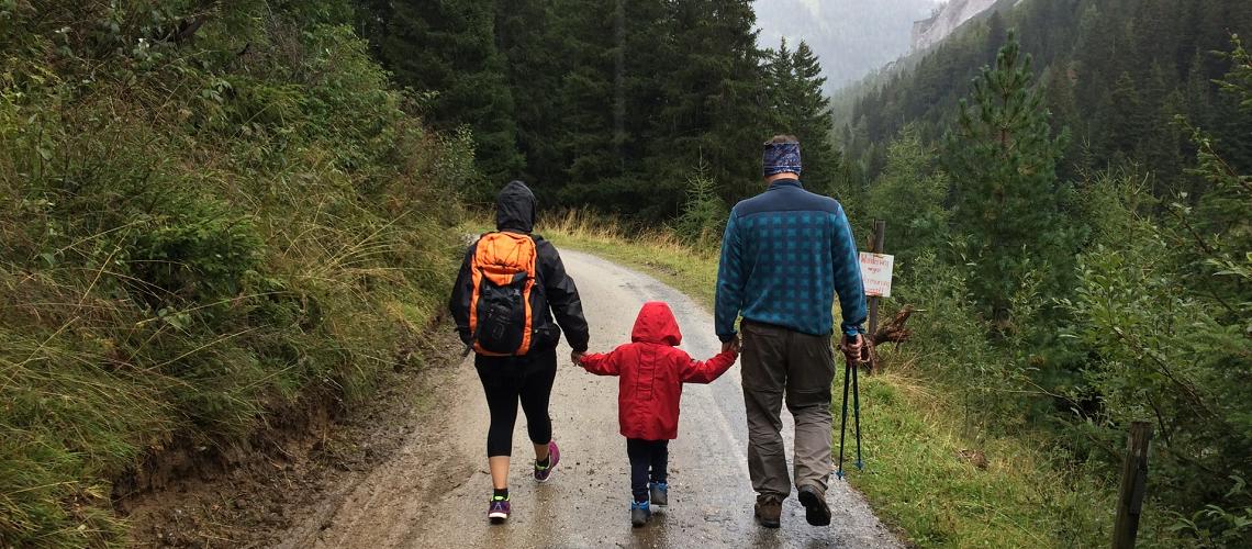 Familie auf Zeit; 3-köpfige Familie geht auf einem Waldweg spazieren
