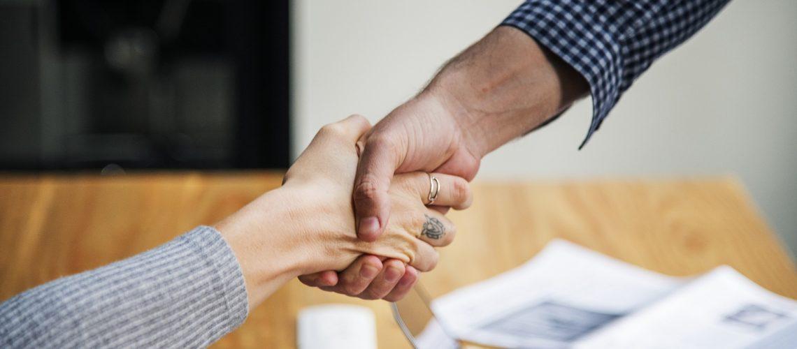Foto zweier Menschen, wie sich die Hände geben zum Projekt CareHoPe - CareLeaver an Hochschulen - Online Peerberatung